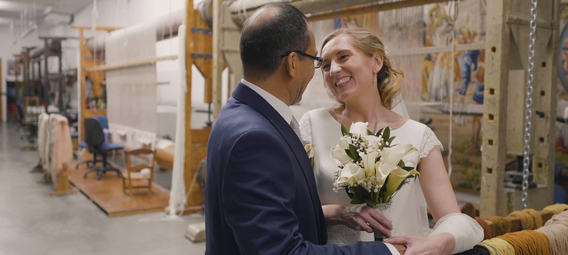Enlace a boda Mer y Jhojan, novios posando en el pasillo central de la fabrica de tapices