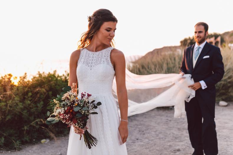 Wedding destination Mallorca, posado novio, novio sujetando velo novia